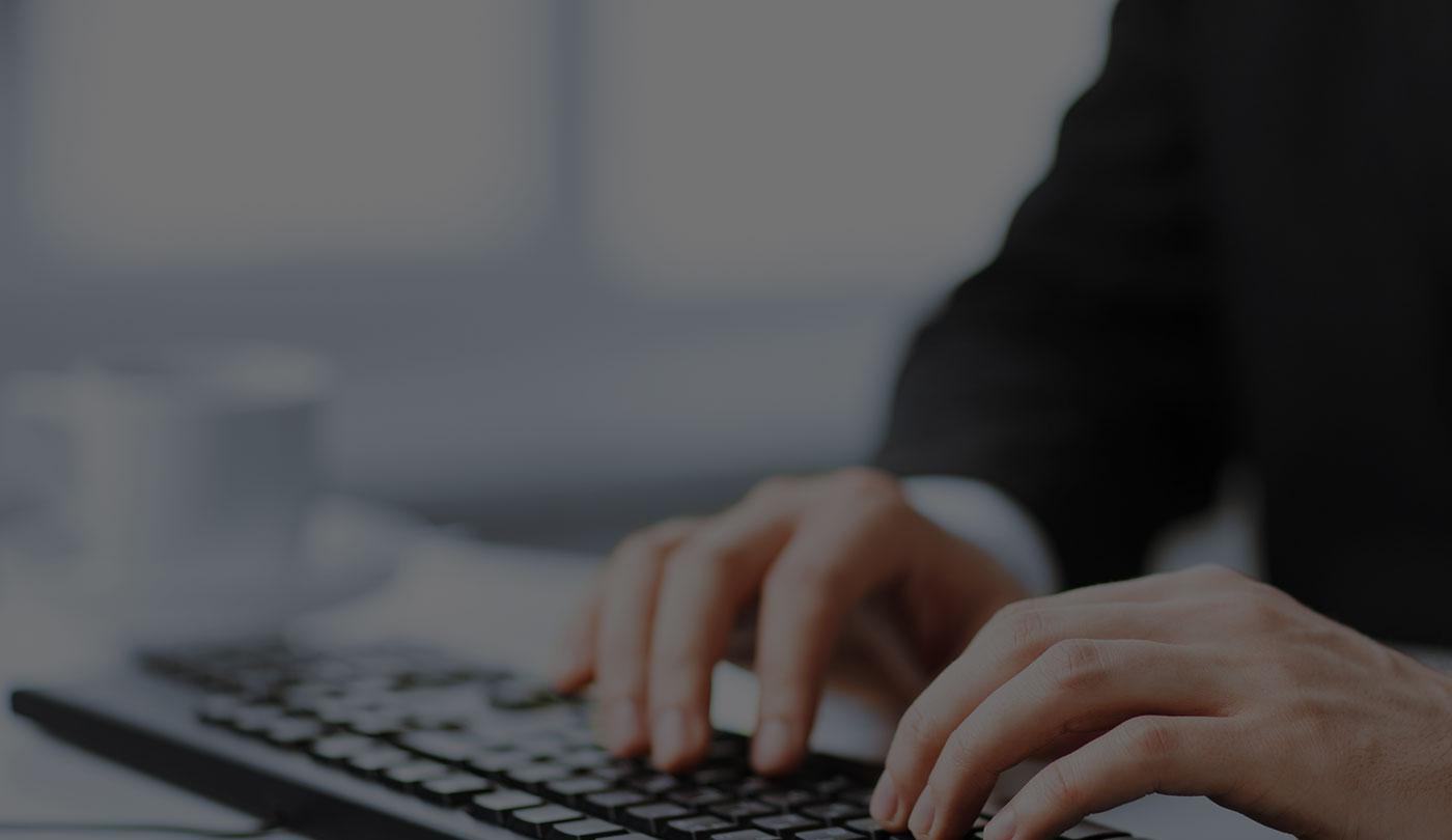 Someone typing up KPIs on a PC - bandv Southampton Marketing Agency